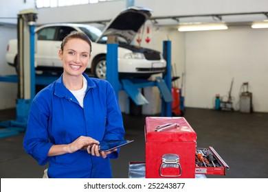 Mechanic smiling at the camera using tablet at the repair garage