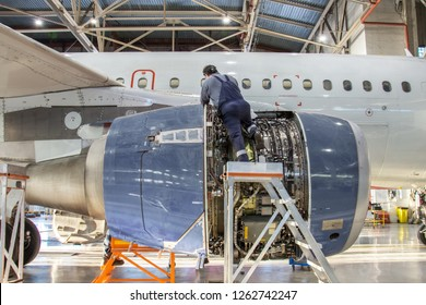 Mechanic specialist repairs the maintenance of engine of a passenger aircraft in a hangar.