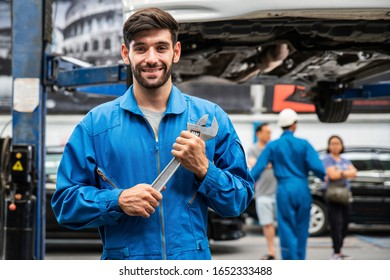 Mechanic standing and hold a wrench with blur his assistant talking with customers in the background. Auto car repair service center. Professional service.
