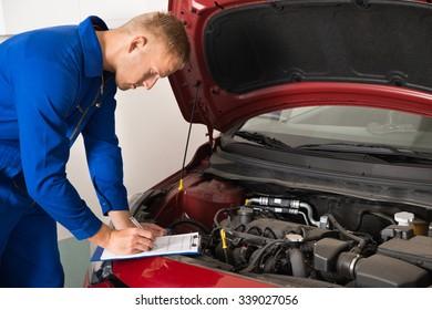 Mechanic Standing Near Car Writing On Clipboard In Garage