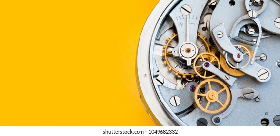 Mechanic stopwatch chronometer mechanism, spring bronze cogs wheels macro view. Shallow depth of field, selective focus. Yellow colorful background. Copy space.