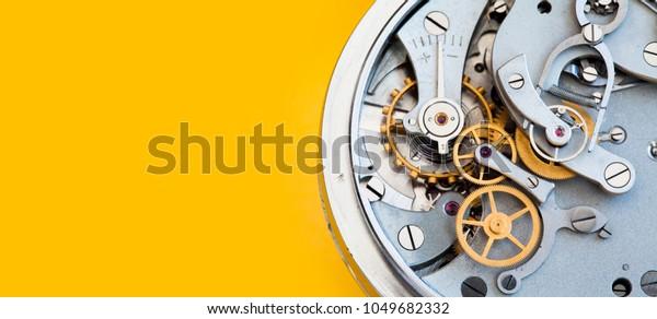 Meccanismo cronometro meccanico cronometro, ingranaggi a molla bronzo ingranaggi vista macro. Profondità di campo bassa, messa a fuoco selettiva. Sfondo colorato giallo. Copia spazio.