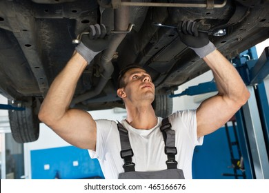 Mechanic with strong hands repair car at auto workstation
