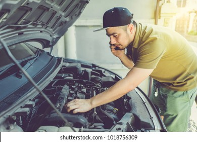 Mechanic, technician man holding clipboard and check the car engine looking at chart note. car service, repair, fixing, checking maintenance working at workshop. inspection vehicle concept.