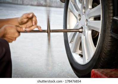 Mechanic technician worker replacing damaged wheel drive vehicle