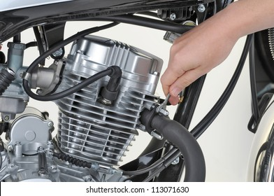 mechanic tightening the exhaust on a motorcycle engine
