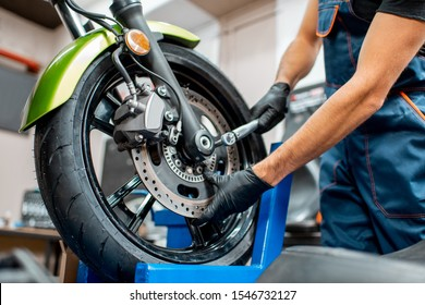 Mechanic tightening motorcycle wheel with a hand wrench during a repairment at the workshop, close-up view