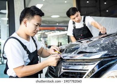 Mechanic with transparent film, car paint protection. Mechanic installs car paint protection film. Install car paint protection film. Car wrap concept.