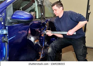 Mechanic trying to open damaged car door.