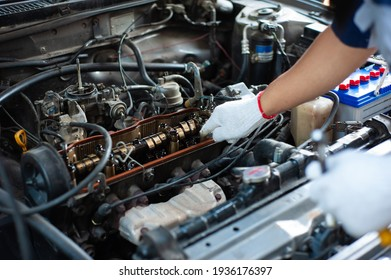 The mechanic is tuning the car's engine.