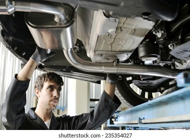 Mechanic Under Car Installing Exhaust Pipe. New generation of sportive mufflers: double Car Exhaust Pipe chromed made of stainless steel