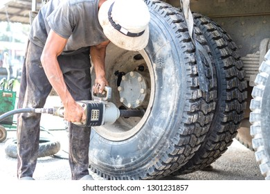 A mechanic use electric drill removing truck tire. Large tire remover.