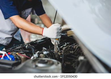 Mechanic uses a wrench to fix the car engine.