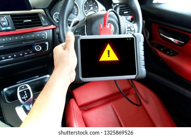 Mechanic is using a car diagnostic tools servicing a car. Diagnostic tools with caution screen being used in red interior car.
