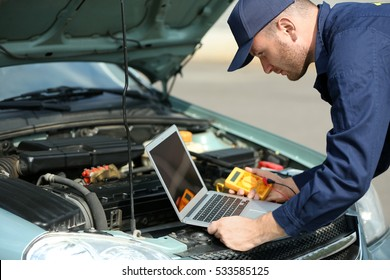 Mechanic using computer diagnostics while repairing car