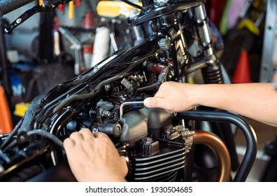 mechanic using Hex Key Wrench working on motorcycle at motorbike garage , concept of motorcycle maintenance and repair . selective focus