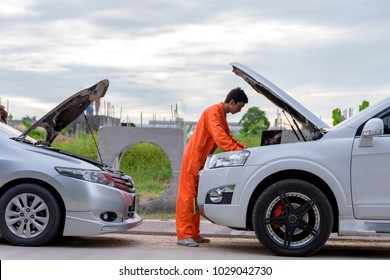 Mechanic using a laptop computer to check a car engine .