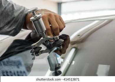 Mechanic using repairing equipment to fix damaged windshield, windshield repairing,