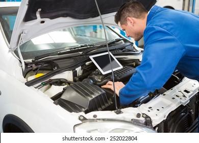 Mechanic using tablet to fix car at the repair garage