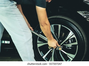 Mechanic using a torque wrench socket and extension on the lug nuts of a car wheel.Standard specification for the plant.Check for safe travel.