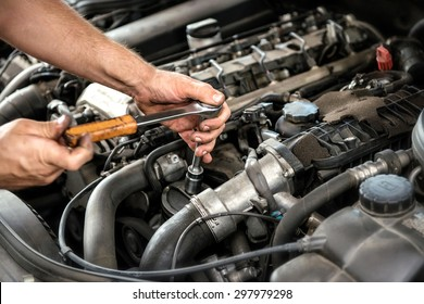 Mechanic using a wrench and socket on the engine of a motor car during a service or repair in an automotive workshop, close up of his hands