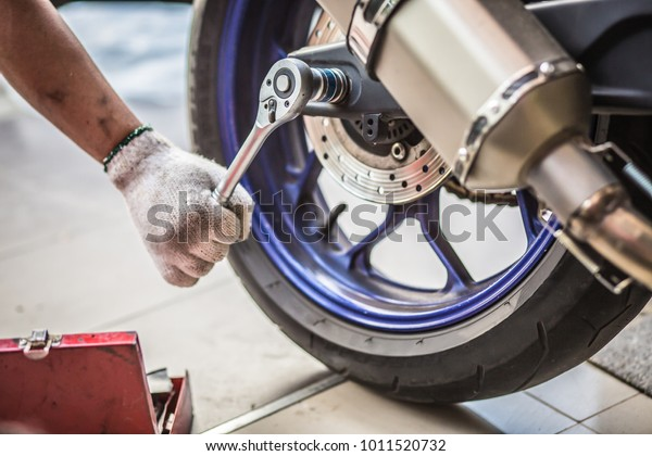 Mechanic using a wrench and socket on the engine of a motorcycle , maintenance,repair motorcycle concept in garage .selective focus