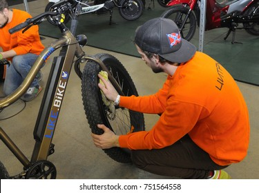 Mechanic wiping wheel of an electric bicycle before exposition. Exhibition ECO DRIVE 2017. March 10, 2017. International Expo center, Kiev, Ukraine