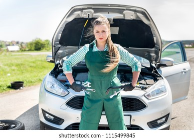 Mechanic woman posing with wrenches and spanners