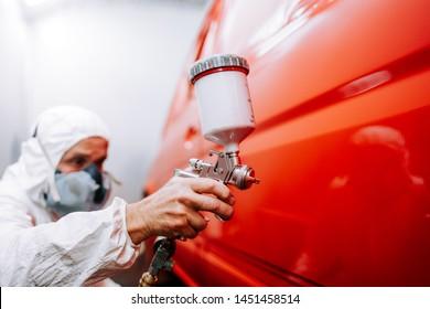 Mechaniker, der ein Auto in einer speziellen Lackierbox anstrich, mit einem vollen Körperkostüm und Schutzausrüstung