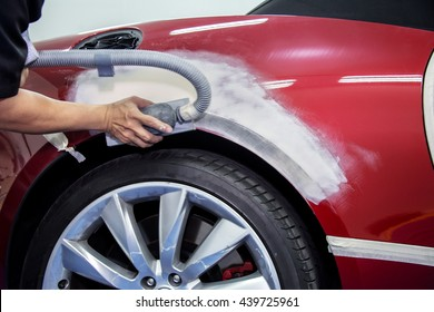 mechanic worker repairman fixing by sanding polishing car body and preparing for painting at station service