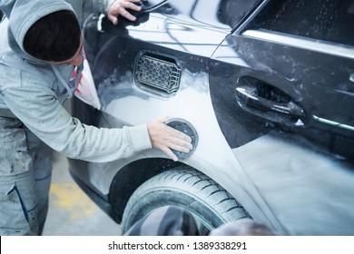 Mechanic worker repairman sanding polishing car body and preparing automobile for painting in workshop garage.