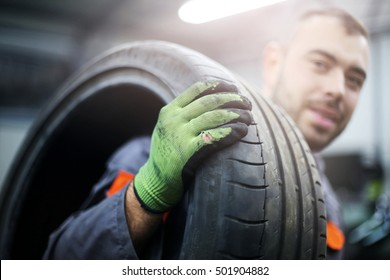 Mechanic working in auto repair shop. Focus is on foreground.