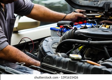 Mechanic working with car spare parts and off road car.