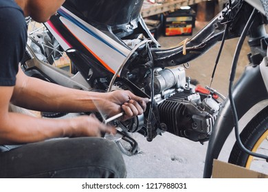 Mechanic working with with motorcycle engine.