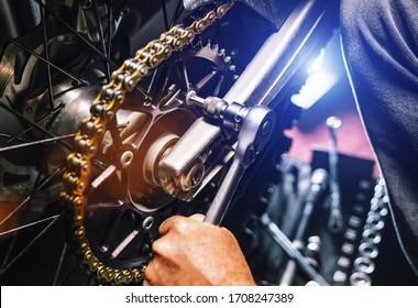 Mechanic working on Motocycle in mechanics garage. Repair service. authentic close-up shot