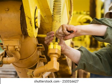 A mechanic works to repair a yellow excavator.