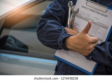 Mechanic with wrench and holding Clipboard check car . Auto mechanic in car repair .