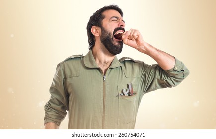 Mechanic yawning over ocher background
