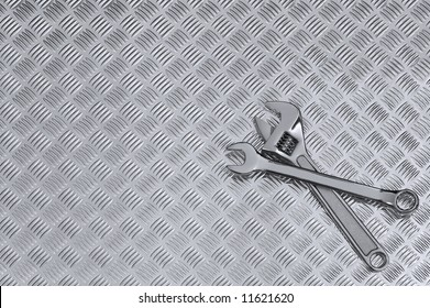 Mechanical background image of two spanners on a checkerplate workbench.