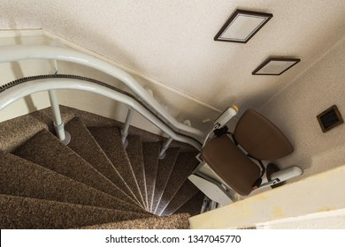 Mechanical chair lift taking disabled or aged people up and down stairs Senior, Stairlift for disabled in a home