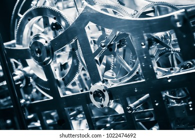 Mechanical clock close-up fragment with shiny gears, blue toned photo