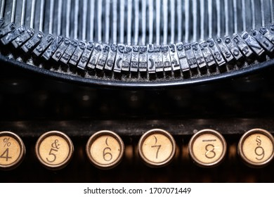Mechanical desktop typewriter with blue typebars and brown keys showing the numbers 4, 5, 6, 7, 8, 9 and other characters