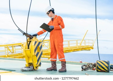 Mechanical engineer inspector is inspecting lifting equipment of pedestal crane on offshore oil and gas wellhead remote platform for yearly preventive maintenance.