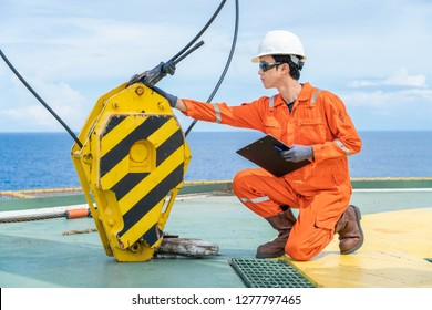 Mechanical engineer inspector is inspecting lifting equipment of pedestal crane at offshore oil and gas wellhead remote platform for yearly preventive maintenance.