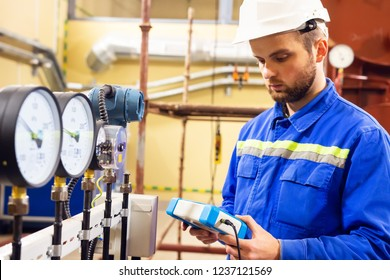Mechanical engineer measuring values of pressure on manometers in oil and gas refinery