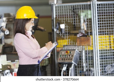 Mechanical engineer taking notes at metallurgy factory