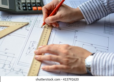 Mechanical engineer at work. Technical drawings. Paper with technical drawings and diagrams.