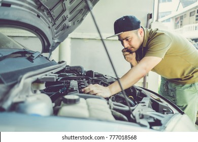 Mechanical fixing car at home. Repairing Service advice by mobile phone. Mechanic, technician man checking car engine. Car service, repair, fixing, maintenance working inspection vehicle concept.