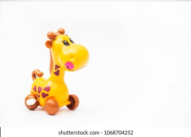 Mechanical giraffe toy. Clockwork plastic toy isolated on left hand with white background.