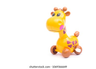 Mechanical giraffe toy. Clockwork plastic toy isolated on right hand with white background.